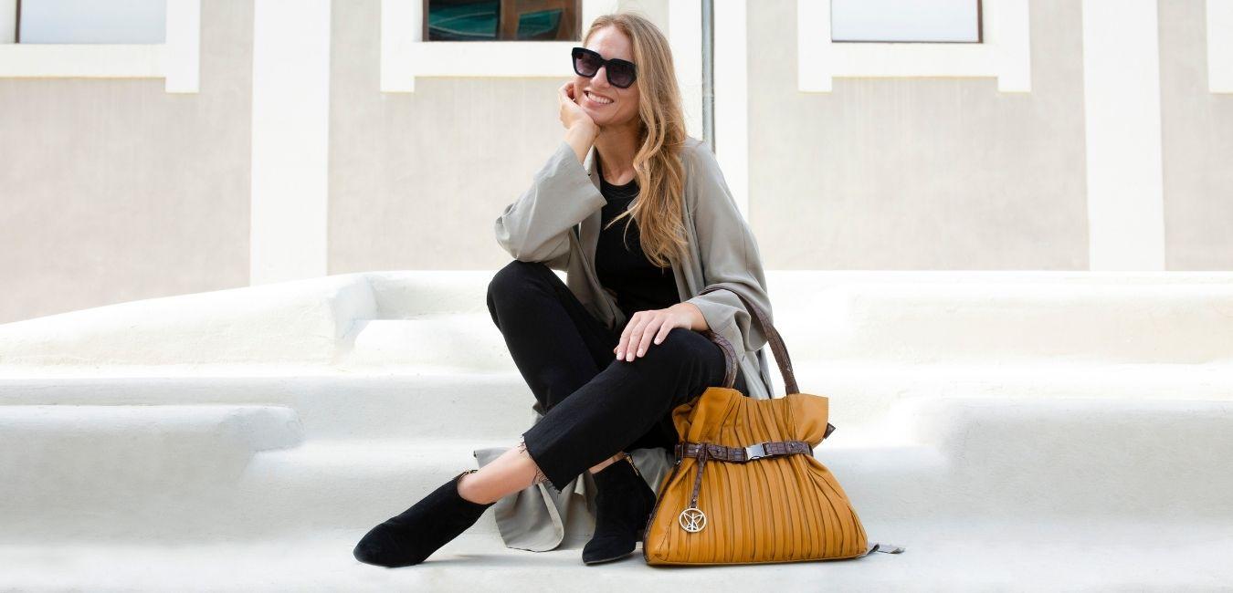 La modelo aparece sentada en unas escaleras en sus manos lleva un bolso de hombro en color mostaza, un bolso amplio y con la capacidad suficiente para llevar contigo todos los objetos necesarios. Un bolso perfecto para el día a día.